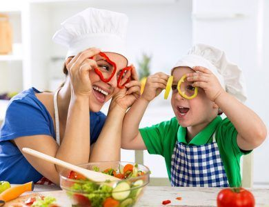 Mamá feliz enseñando a su hijo a comer de forma saludable para evitar obesidad infantil