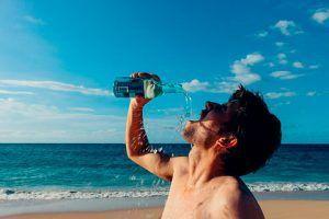 Hombre sediento tomado agua en la playa