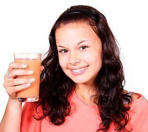 mujer joven tomando el jugo de fruta